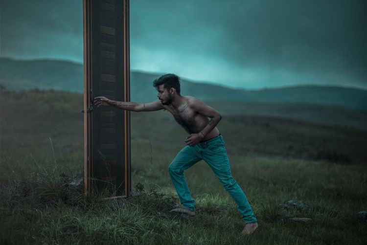 Full length of shirtless man standing on field against sky