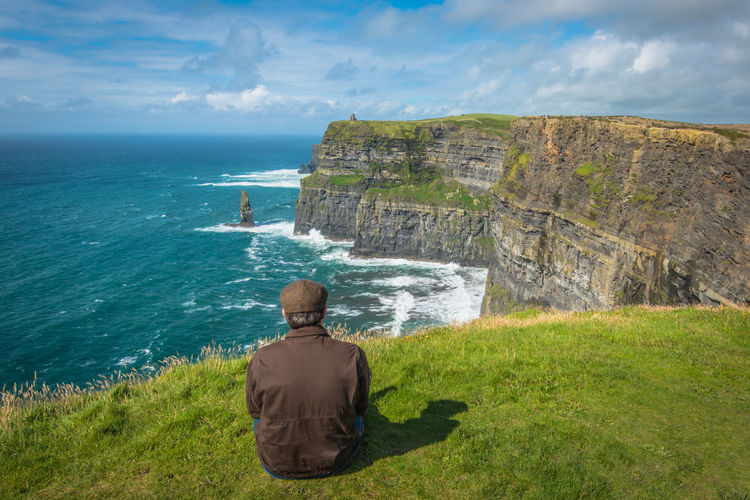 Rear View of Irish Man in Tam O'Shanter Looking at the Cliffs of Moher Cliffs Cliffs Of Moher  Ireland Iris Man Sitting Tam O' Shanter Travel Beauty In Nature Horizon Over Water Irish Man Nature One Man Only One Person Rear View Scenics Sky Travel Destinations Vacation Lost In The Landscape