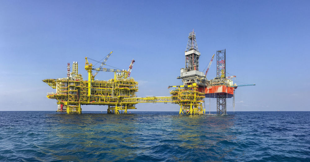 Oil and gas industries. View of red jack up rig drilling on top of well head platform in the middle of the sea. New oil and gas platform installation with central processing platform at North Malay Basin field. Commissioning Construction Industrial Production RISK Transportation Commercial Compensation Drilling Engineering Exploration Hazard Installation Job Mega Structure Occupation Occupational Safety And Health Offshore Platform Oil And Gas Platform Progress Rig Safety Source Technology