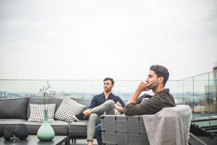 Men sitting on railing against sky