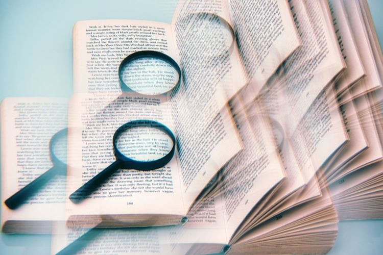 Digital composite image of magnifying glass and book on blue background