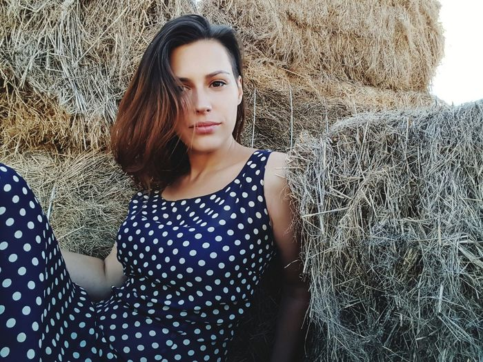 Portrait of young woman relaxing by hay bales on field