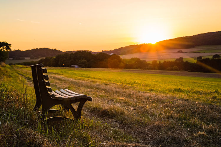Bench on field against sky during sunset