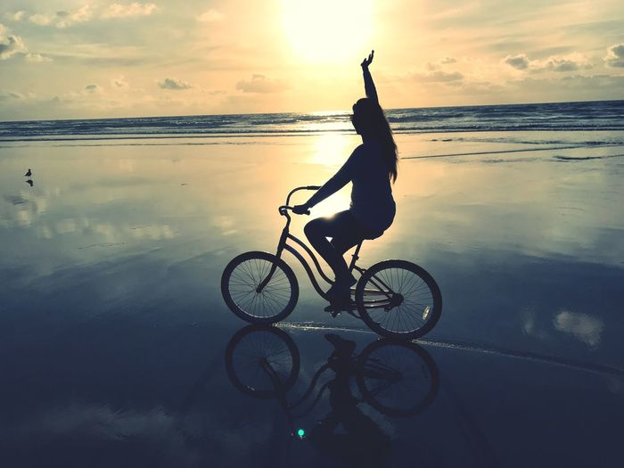 Woman riding bicycle at beach against sky during sunset