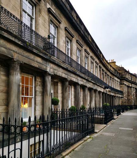 Buildings by street against sky