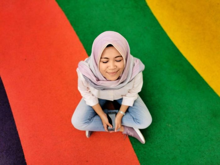High angle view of woman with eyes closed wearing hijab while sitting on colored floor