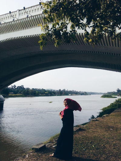 Portrait of smiling young woman standing on riverbank under bridge