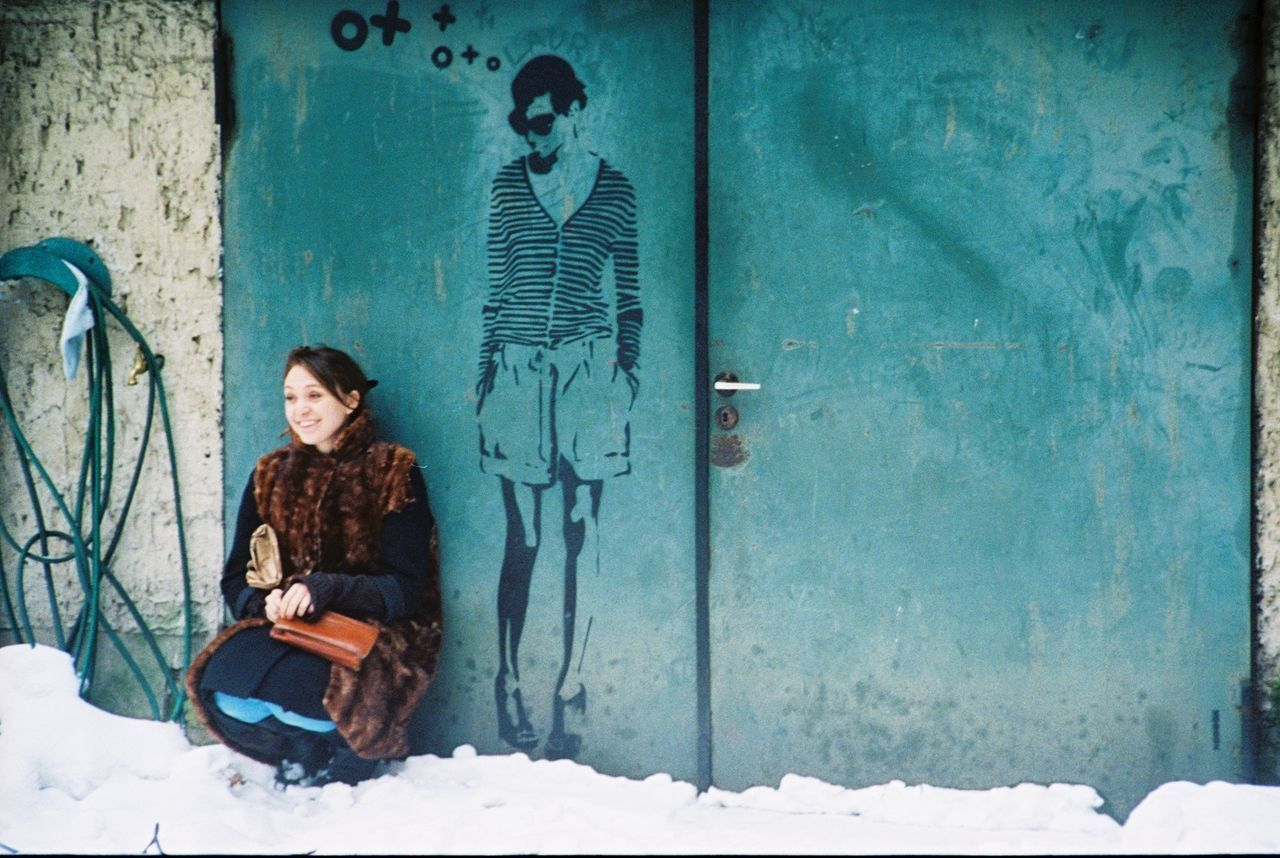 Beautiful young woman sitting against closed doors in winter