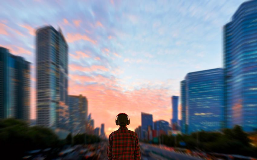 Rear view of man in city against sky during sunset