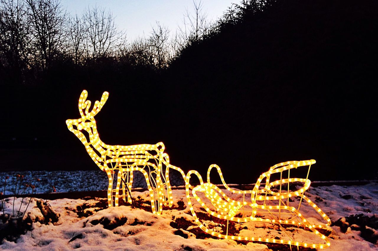 Illuminated reindeer sleigh on snowy landscape against clear sky
