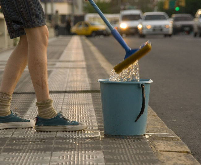 Low section of man mopping sidewalk