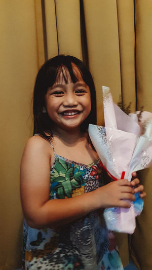 Little girl is happy receiving a bouquet of flower on her birthday. 5 Years Old Asian  Asian Kid Asian Kids Birthday Girl Childhood Cute Day Elementary Age Flower Bouquet  Girls Happiness Happy Kid Indoors  Lifestyles Little Girl Looking At Camera Malaysian One Person People Portrait Real People Smiling Standing Young Girl