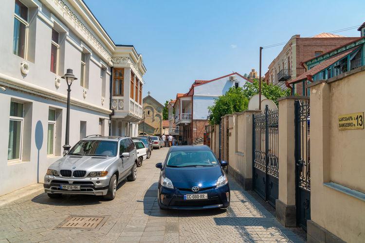 Cars on street by buildings against blue sky