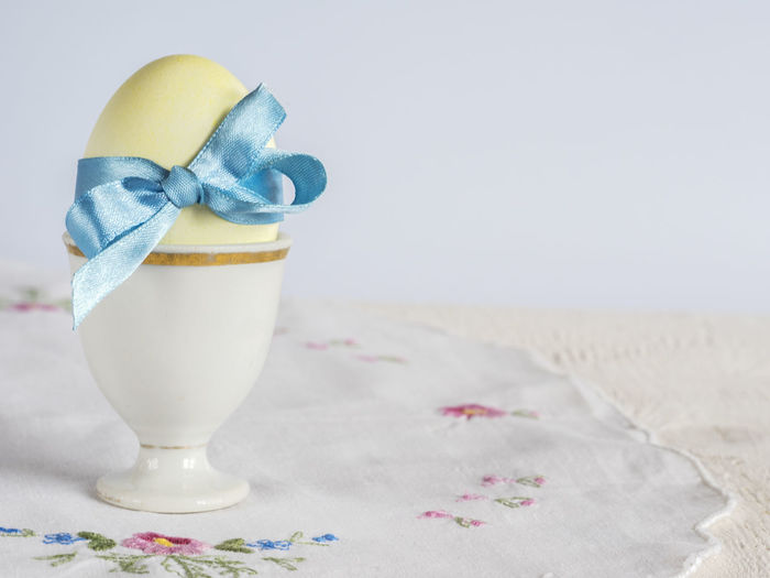 Easter egg with blue bow on an embroidered napkin Blue Bow Carefree Drink Easter Egg Embroidered Focus On Foreground Food And Drink Freshness Napkin No People Non-alcoholic Beverage Refreshment Ribbon Still Life Summer
