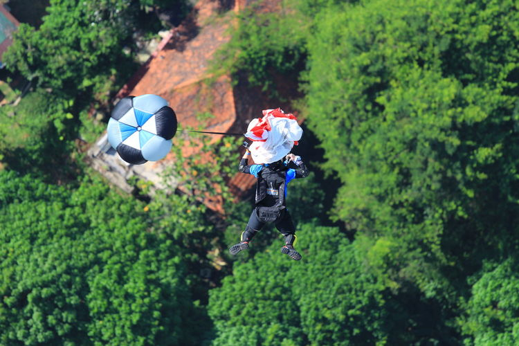 High Angle View Of Man Base Jumping With Against Trees