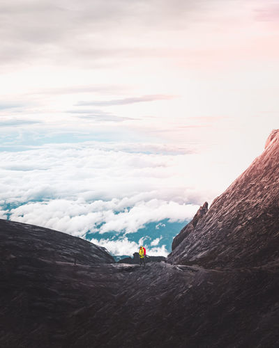 Hiker standing on mountain against sky