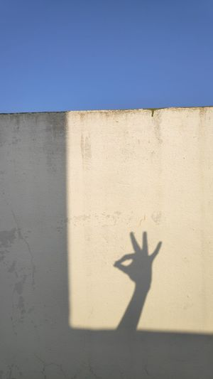 Shadow of people on wall against blue sky
