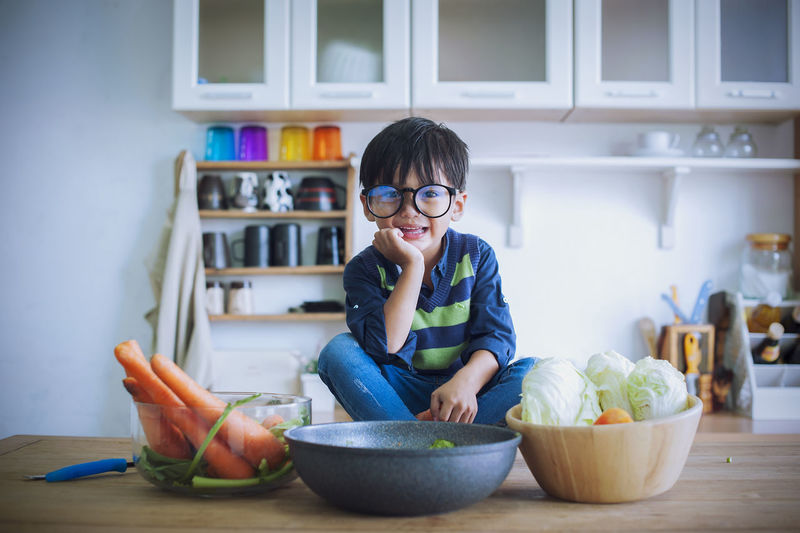 boy; cooking; food; cute; cook; chef; happy; fun; cheerful; funny; thinking; childhood; culinary; idea; happiness; concept; eating; thoughtful; delicious; preparation; nutrition; fastfood; dinner; expression; atmosphere; health; invent; joy; creative; vitamin; surprised; nutrient; serious; entertainment; recipe; friendly; little chefs; kitchen table; satisfied; chef cooking; mealtime; joyful; catering; household; lunch; gourmet; courses; advertising; ideas; process; charismatic; youngster Child Childhood Eyeglasses  Lifestyles Food Wellbeing Bowl Healthy Eating Casual Clothing Food And Drink Indoors  Portrait Front View Glasses Looking At Camera One Person Real People Domestic Room Innocence