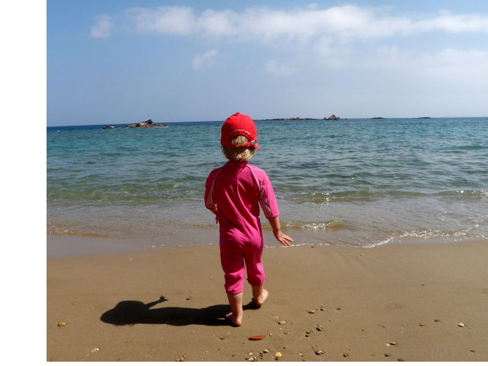 Rear View Of Child Walking Towards Sea Shore Against Sky