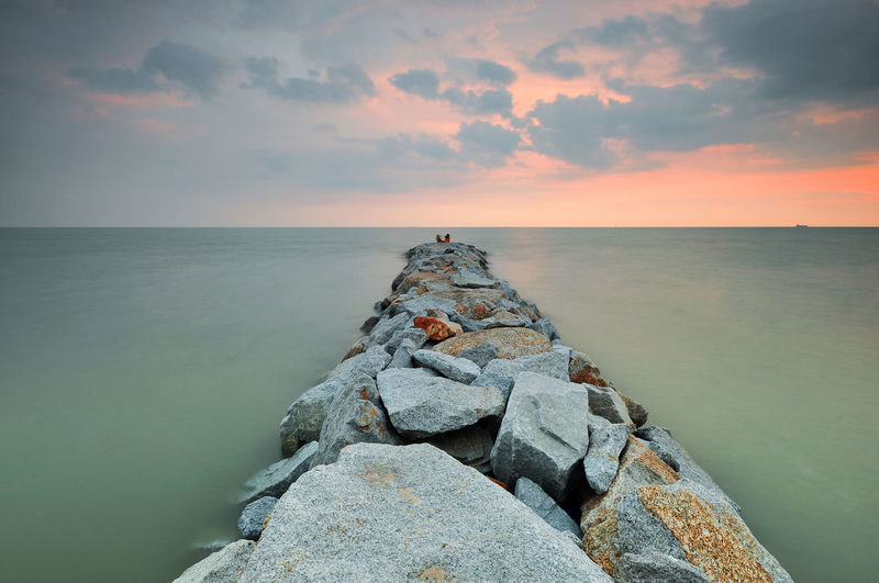 Groynes by sea against cloudy sky during sunset