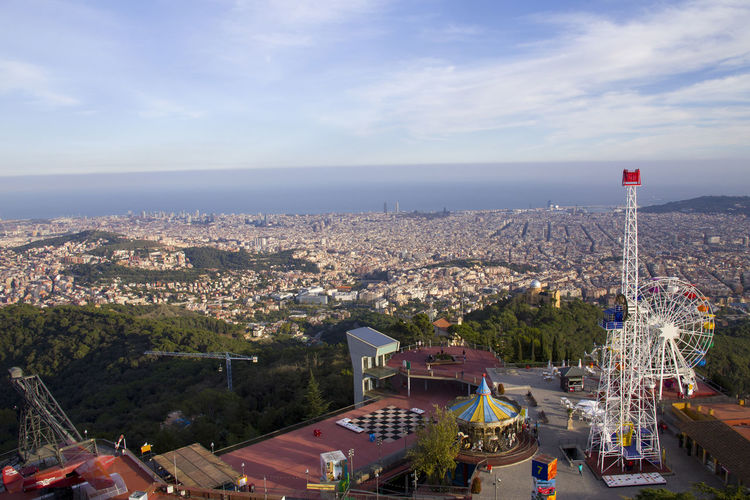 Highest viewpoint featuring an amusement park depicting views of the city and sea. Sunny day in Tibidabo, Barcelona Architecture Built Structure Building Exterior City Sky Building Cityscape Nature Cloud - Sky Residential District High Angle View Day No People Outdoors Travel Destinations Mountain Town Transportation Tibidabo Amusement Park Ferris Wheel Barcelona Top View