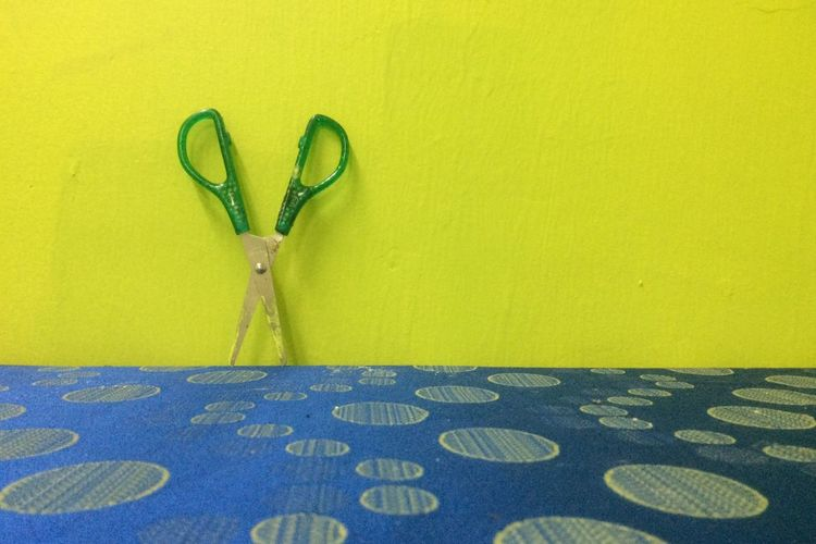 Scissors On Table Against Green Wall