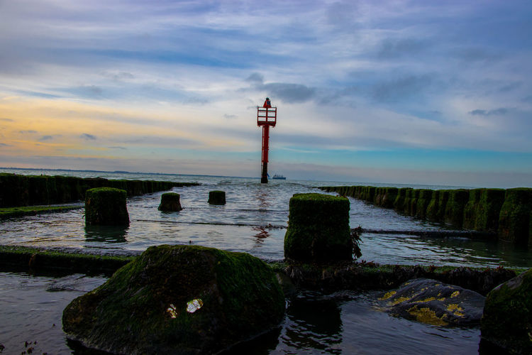 Lighthouse on wooden post by sea against sky
