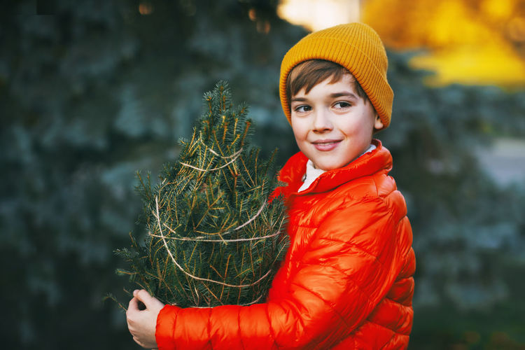 A boy in a bright orange jacket and yellow hat holds a purchased christmas tree in his hands,