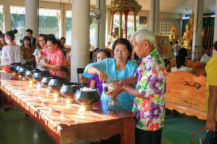 People are making merit in the bowl. Offer Food To Monk Tradition Buddhist Tradition Dedication Of Merit Leisure Activity Make Merit Measured People Philanthropy Real People Religion Senior Adult Senior Men Senior Women Standing Table Togetherness Villager Women