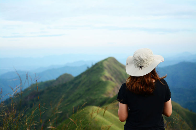 Rear View Of Woman Wearing Hat Looking At Mountains Against Sky