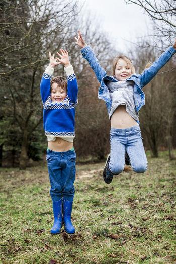 Full length portrait of happy siblings jumping on field