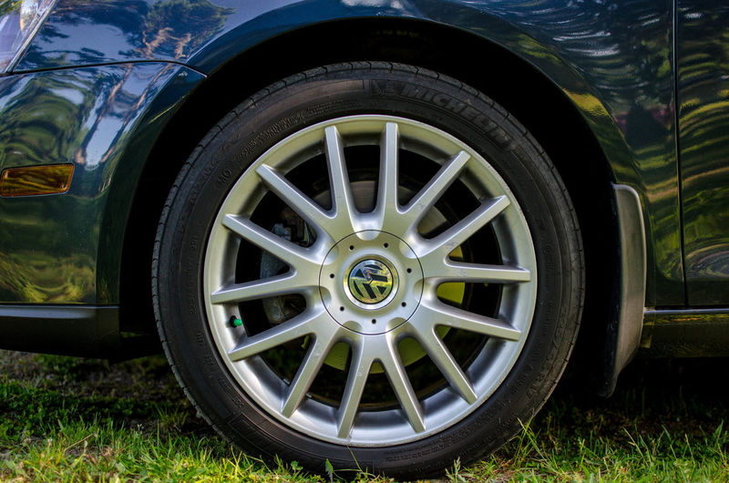 Wheel Mode Of Transportation Transportation Tire Land Vehicle Car Motor Vehicle Travel Day No People Stationary Land Grass Close-up Outdoors Nature Field Plant Shape Parking Silver Colored Spoke VW Jetta VW Jetta