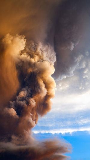 Smoke emitting from volcanic against sky