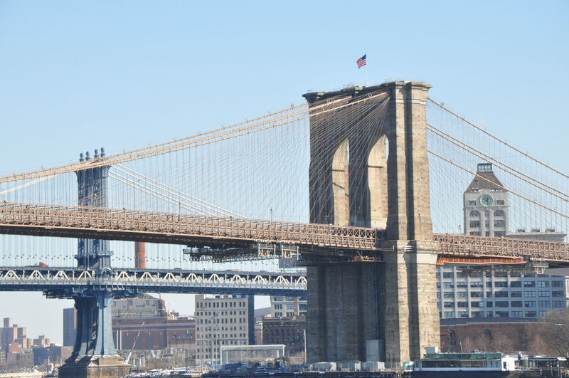 LOW ANGLE VIEW OF BROOKLYN BRIDGE FROM NEW YORK CITY