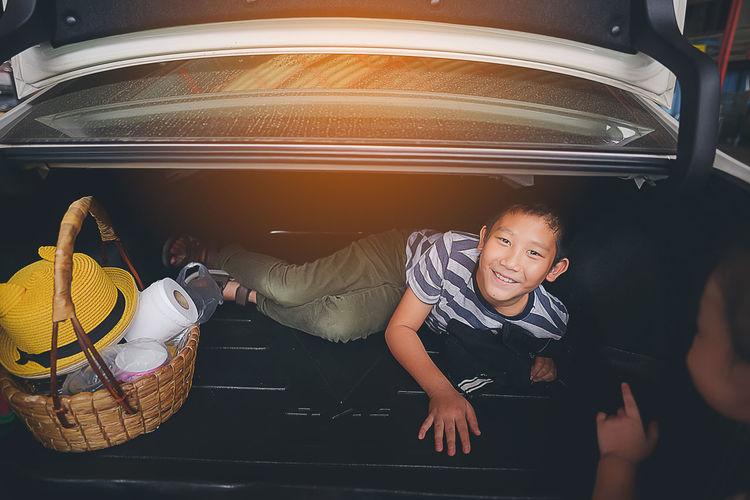 Portrait of boy lying in car trunk