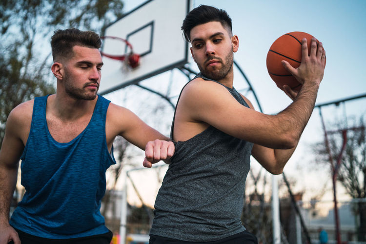 Close-up of men playing basketball outdoors