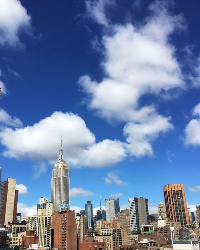 Empire State Building In City Against Cloudy Sky