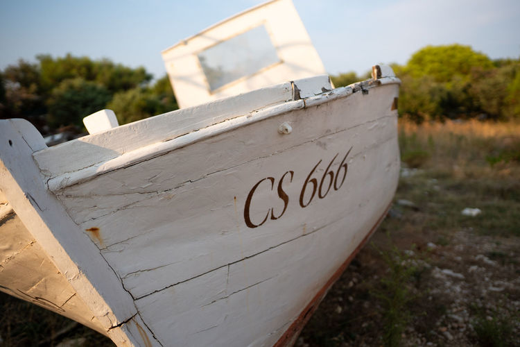 Text Communication Western Script Day Focus On Foreground No People Nature Nautical Vessel Outdoors Close-up Plant Land Sky Information Sign Transportation Paper Sunlight Information Sign Beach Message Boat Wreck Fisherman Boat