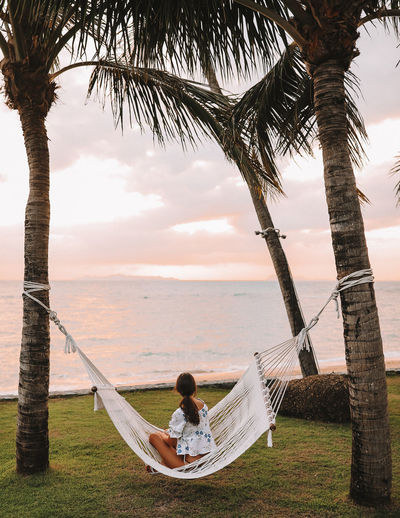 Woman in hammock watching the sunset One Person Real People Leisure Activity Sitting Tree Trunk Trunk Nature Lifestyles Palm Tree Hammock Young Adult Casual Clothing Beauty In Nature Outdoors Resort One Woman Only Girl No Face Travel Thailand Sea Sunset Long Hair ASIA Pink Clouds