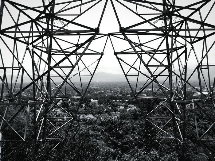 Metallic electricity pylon against city