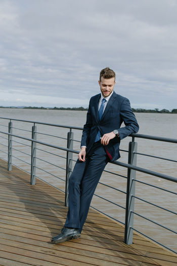 Handsome Man Leaning On Railing Against Sea