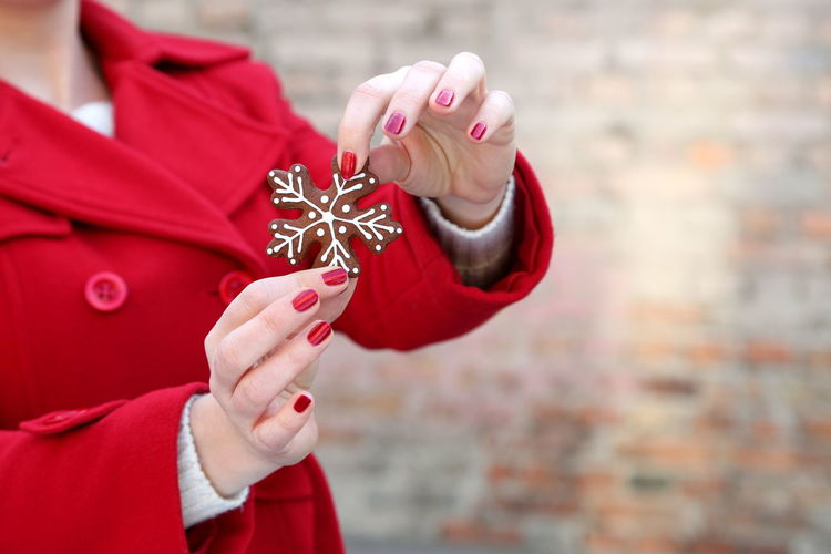 Midsection of woman showing snowflake shape cookie during christmas