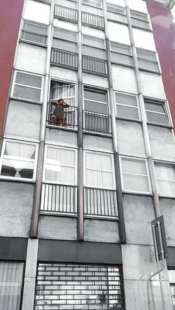 Architecture Building Exterior Built Structure Low Angle View Window Building In A Row Repetition Color Splash Architectural Feature Outdoors Modern Office Building One Person Tall - High Watching Watching Out Of Window Watching Out Apartment Apartments Smoking Smoking Time Smoking Kills Cigarette  Exterior