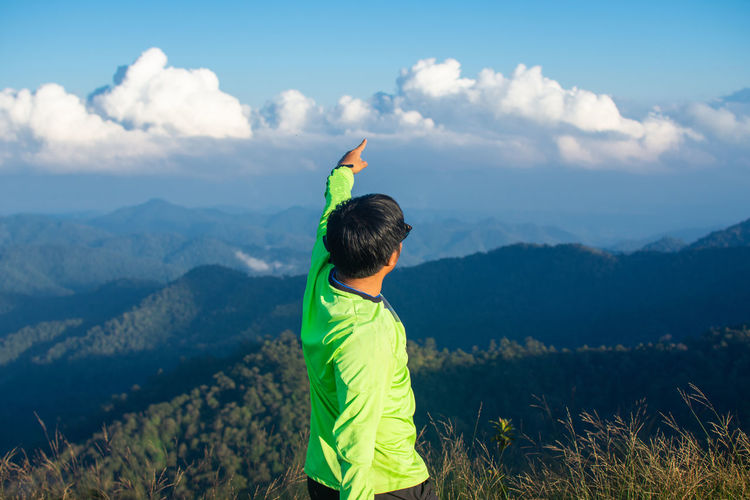 Side view of man with hand raised standing on mountain against cloudy sky