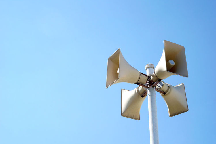 Low angle view of megaphones on pole against clear blue sky