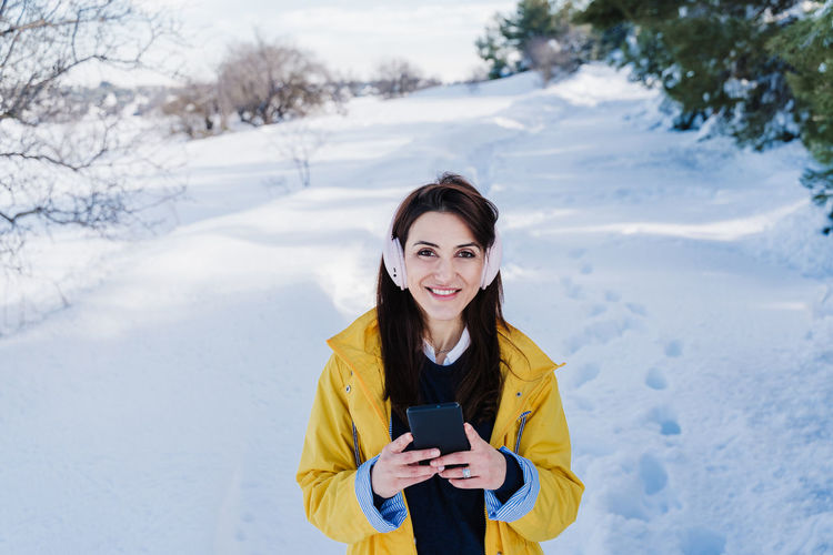 Portrait of smiling woman standing on snow covered