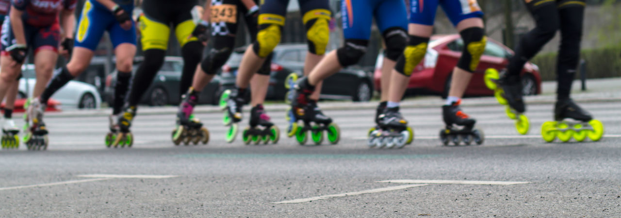 Low section of people inline skating on road