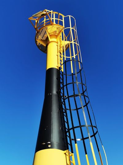 Low angle view of yellow tower against clear blue sky