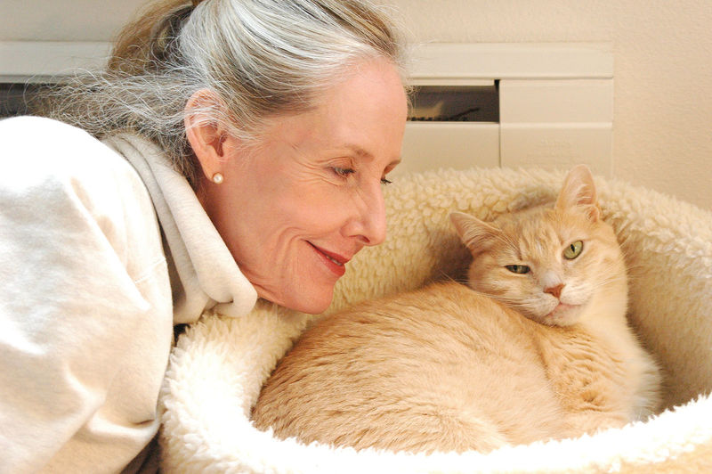 Portrait of woman with cat relaxing at home
