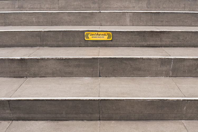 """Paved grey public steps with a yellow """"Beware your step"""" caution sign. Beware Caution City Copy Space Grey Lines Paved Paving Plain Public Space Sign Stairs Step Up Steps Up Warning Yellow Architecture Text No People Western Script Communication Built Structure Wall - Building Feature Day Transportation Staircase Public Transportation Subway Station Outdoors Arrow Symbol Information Tile High Angle View Leaving Concrete"""